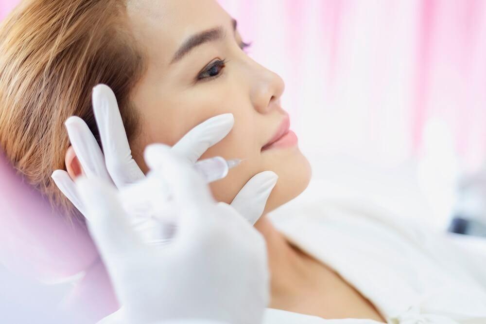 Mulher recebendo procedimento odontológico após anestesia odontológica.