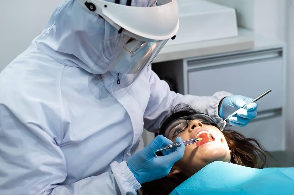 Profissional da odontologia vestido com todos os EPIs enquanto realiza procedimento