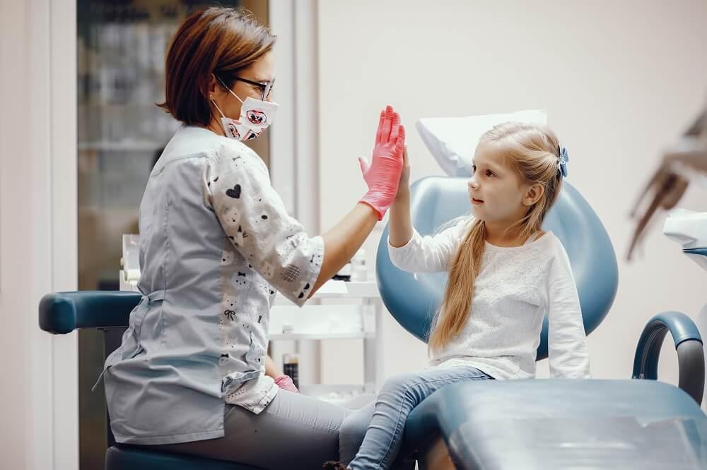Dentista e criança se comprimentando
