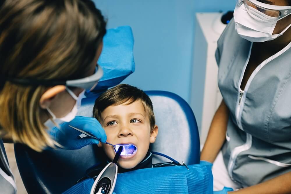 Menino pequeno recebendo atendimento odontológico