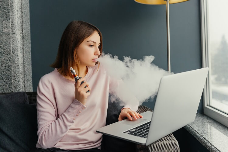 Mulher jovem fumando vaper enquanto mexe em notebook