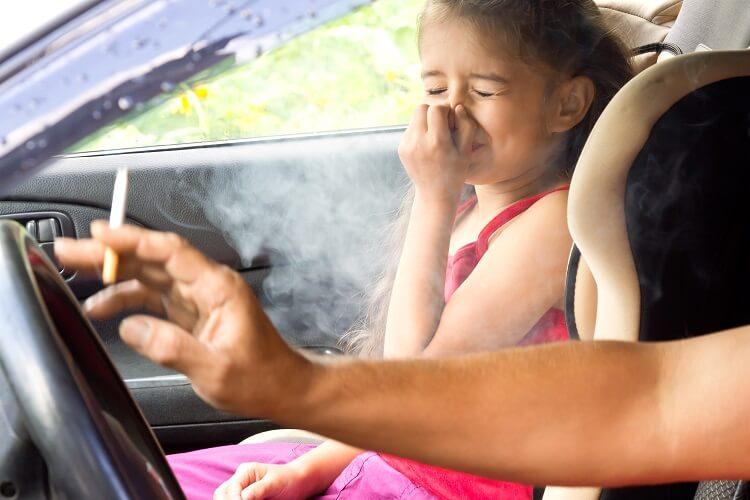 Menina dentro de carro tapando nariz ao lado de adulto fumante