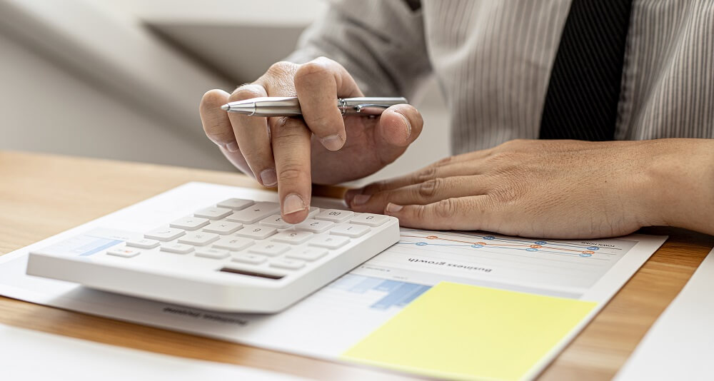 Mãos masculinas mexendo em calculadora