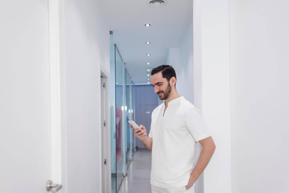 Dentista mexendo no celular em corredor de clínica.