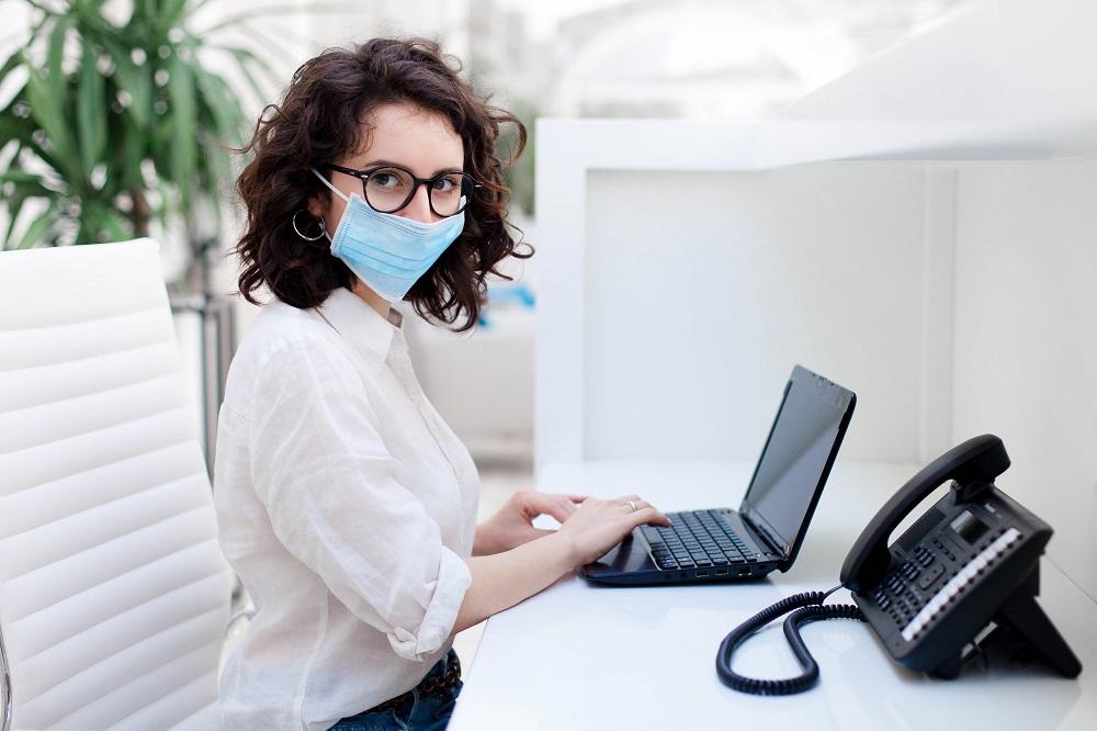 Secretaria em consultório odontológico respeitando as diretrizes de biossegurança em odontologia