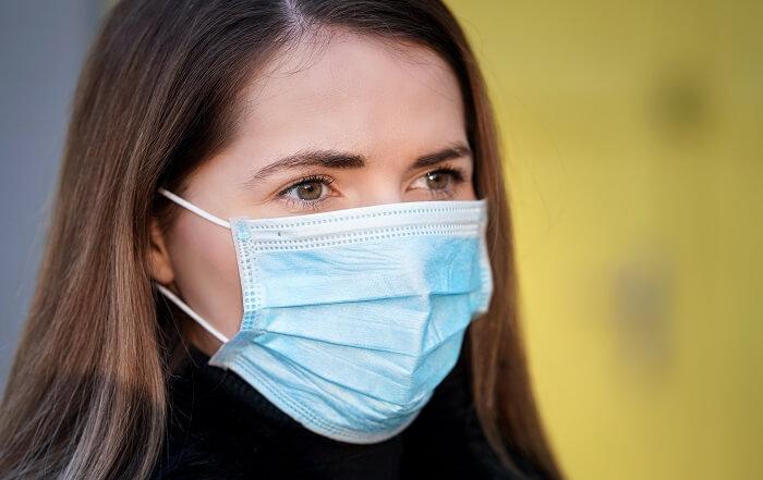 Rosto de mulher utilizando máscara cirúrgica