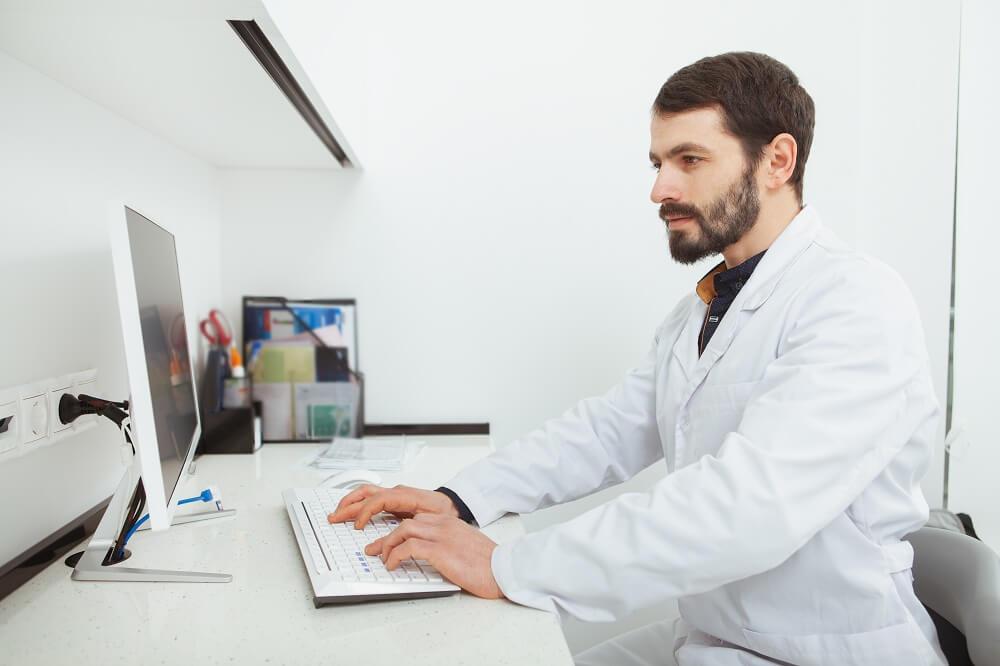 Dentista digitando em computador