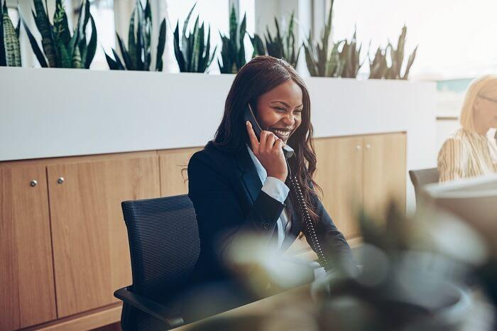 Mulher negra recepcionista falando ao telefone e sorrindo