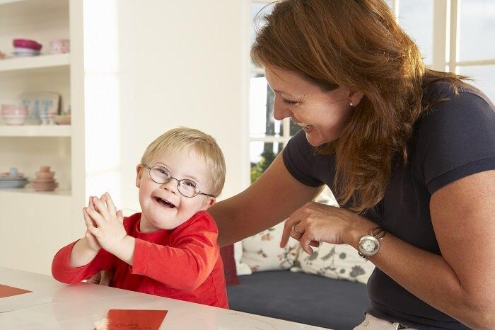 Bebê branco com síndrome de down recebendo atendimento por mulher