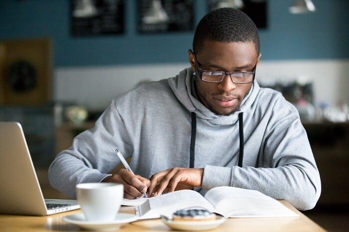 Homem negro estudando por anotações