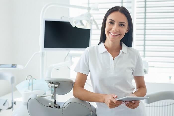 Mulher branca dentista em consultório odontológico