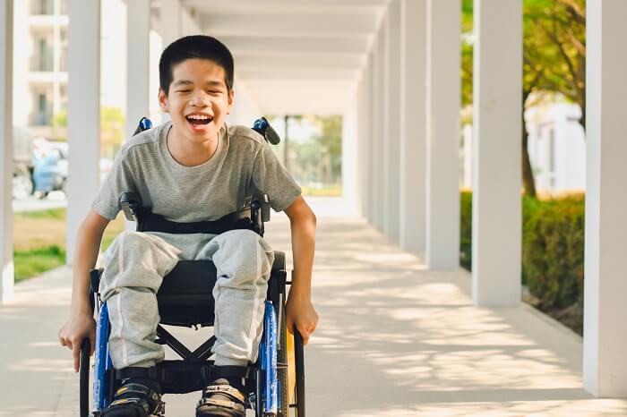 Menino asiático em cadeira de roda