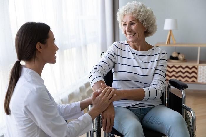Idosa branca em cadeira de roda recebendo atendimento de mulher
