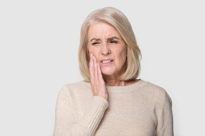 Mulher branca de meia idade com dores