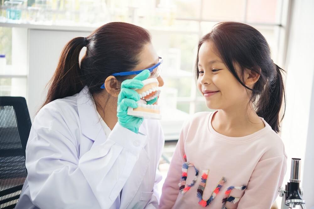 Menina asiática conversando com dentista