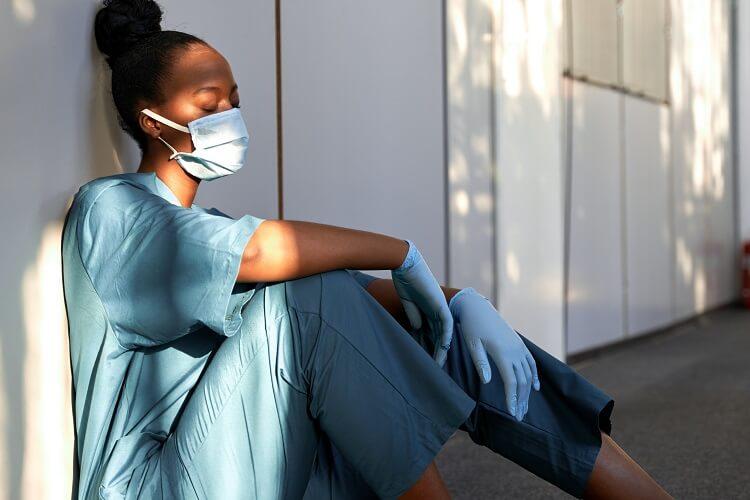 Mulher negra vestida com roupas hospitalares sentada no chão, cansada.