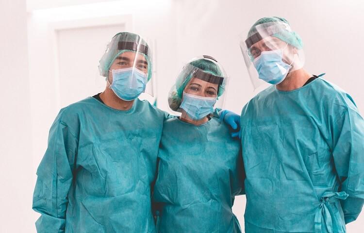 Três dentistas com EPIs contra o coronavírus