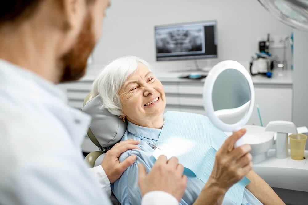 Senhora em consultório odontológico olhando dentes no espelho