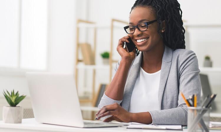 Mulher negra em notebook enquanto faz telefonema