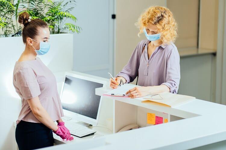 Mulher assinando caderno em recepção de consultório