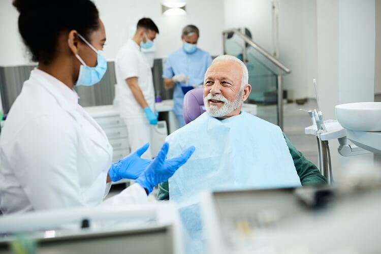 Dentista conversando com paciente idoso